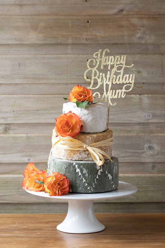 Adorable 3 tier celebration cheese cake with decorative orange flowers, perfect for a birthday.