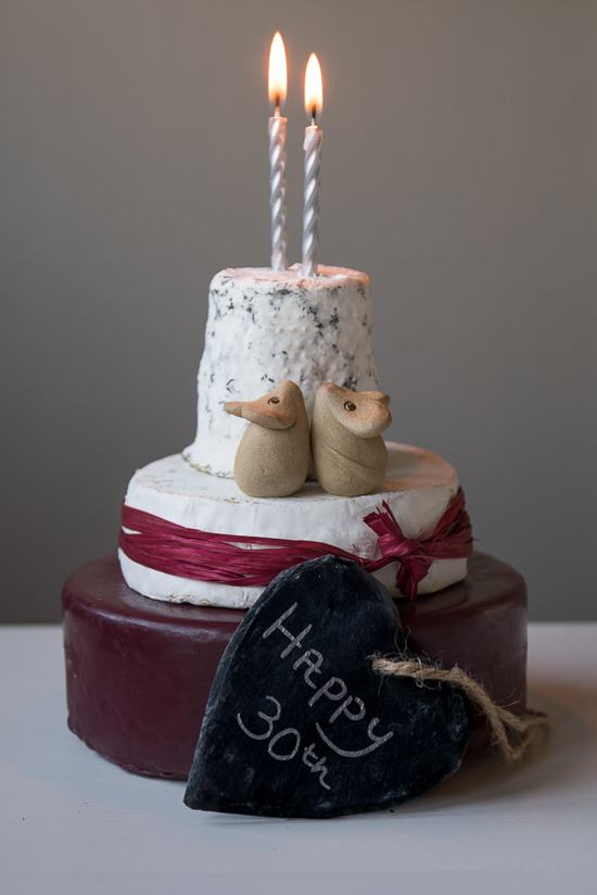 "3 Tier celebration cheese cake with red raffia and two silver candles. including a heart shaped piece of grey slate with the words ""Happy 30th"" leaning against the cheese cake."