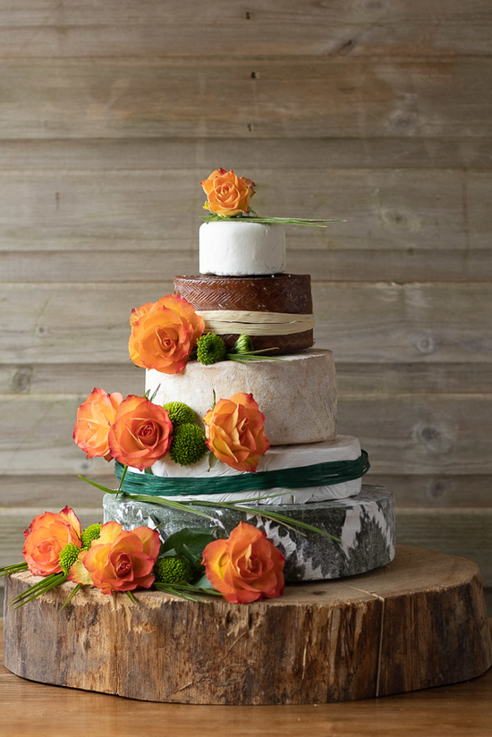 The Ava Wedding Cheese cake has 5 tiers with beautiful orange decorative roses surrounding the cake. two of the layers is wrapped in forest green and ivory raffia.