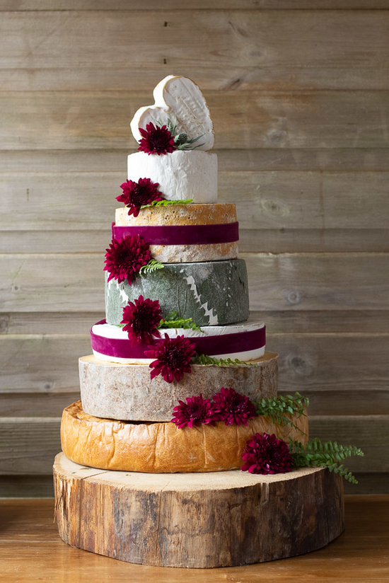 7 tier cheese and pork pie cake, the base of the cake is the pork pie and the rest is cheese. This cake has decorative red flowers and ribbons. The top cheese is heart shaped.