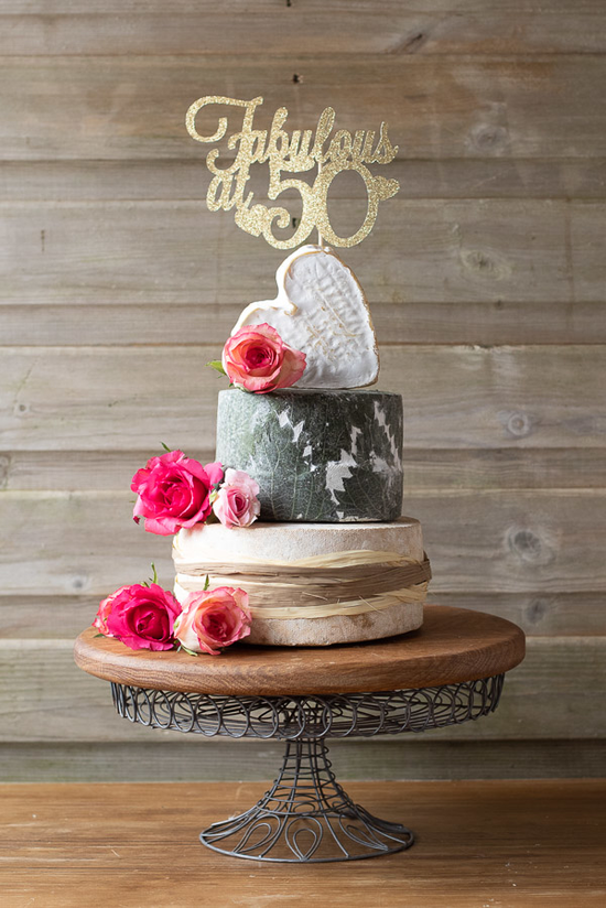 Our 3 tier charming cheese cake is perfect for a special occasion. the tiers include, heart shaped Stithians, Yarg and Coeurs Neufchatel. Decorated with pink roses and natural raffia.
