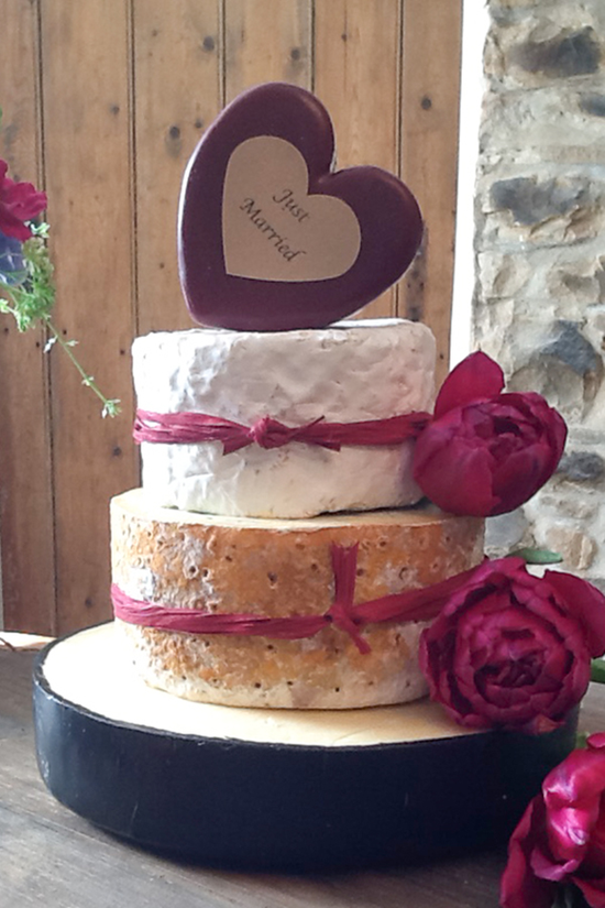 4 tier cheese cake with red decorative flowers and red raffia going round the cheese. Top tier is heart shaped cheese.