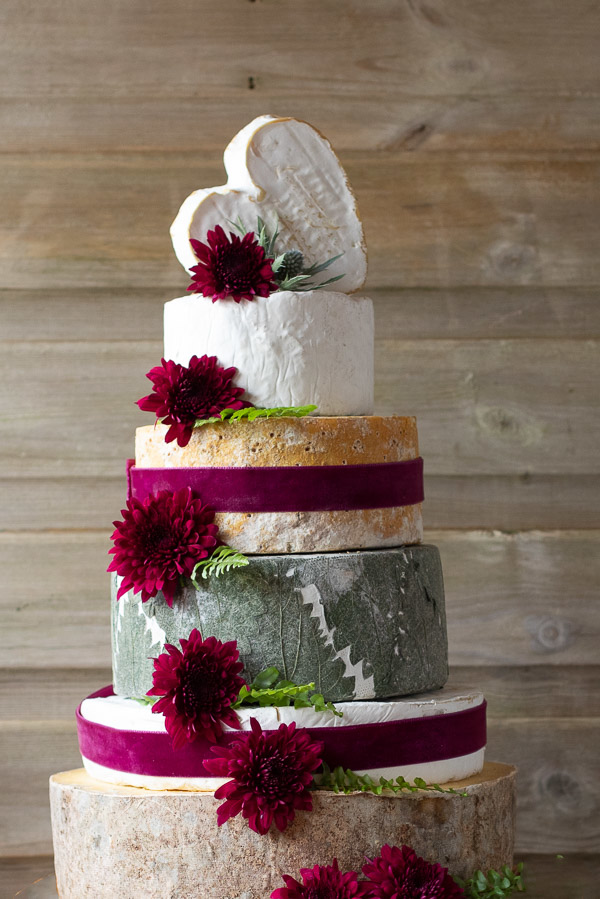 "The beautiful 6 tier ""Behold"" Wedding cake featuring mature cheddar, Cornish Brie, Yarg, stilton, White nancy and Coeurs Neufchatel.  Decorated with Red ribbons and flowers."