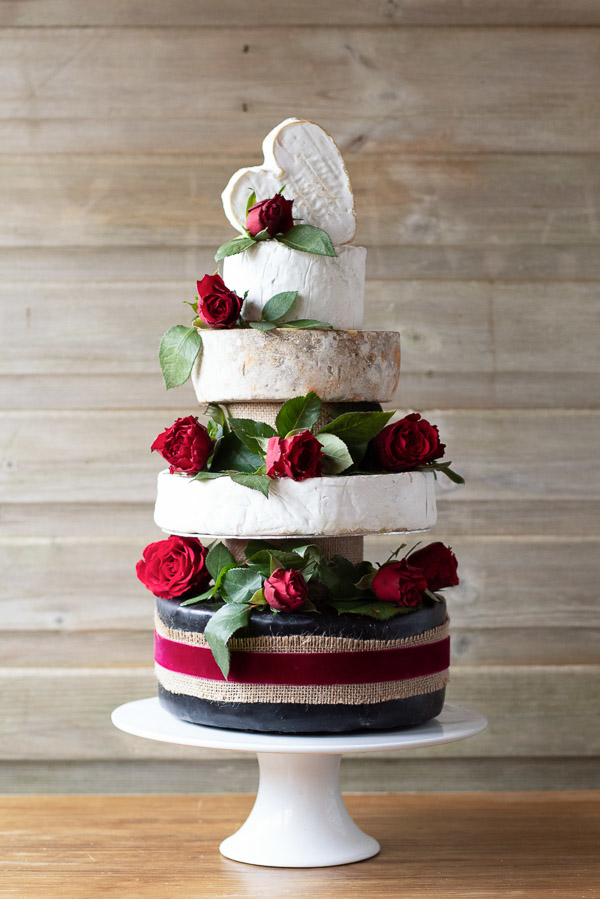 This absolutely stunning Cheese Cake has 5 tiers, one of which is heart shaped and at the top of the cake. This cake is decorated with gorgeous red roses and greenery.