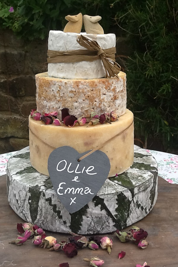 "The Cornish Yarg Delight features 4 tiers including, Cornish Yarg, Stilton, Camembert and Chedder. This cake is decorated with rose buds, a grey slate with the names ""Ollie & Emma"" on, two decorative mice on the top. and ivory raffia around the top tier."