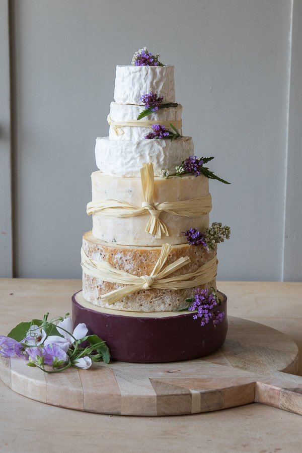 Our stunning Delish Cheese cake has 6 tiers and is decorated with ivory raffia and wonderful purple flowers.