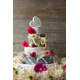 5 tiers of various types of cheese with decorative pink, red and green flowers and a light ivory coloured raffia.